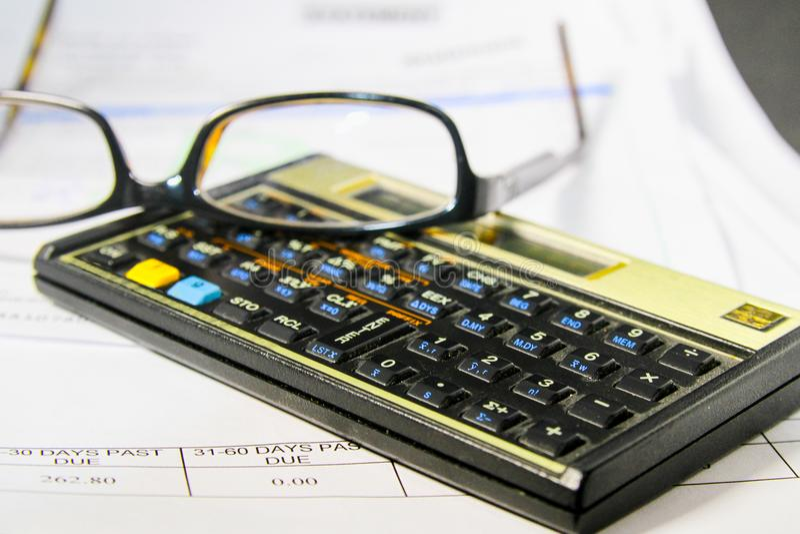 Contas pagando com uma calculadora e vidros de leitura foto de stock