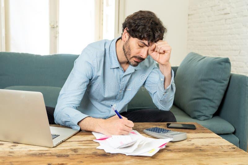 Contas pagando do homem irritado como em casa com portátil e calculadora imagem de stock