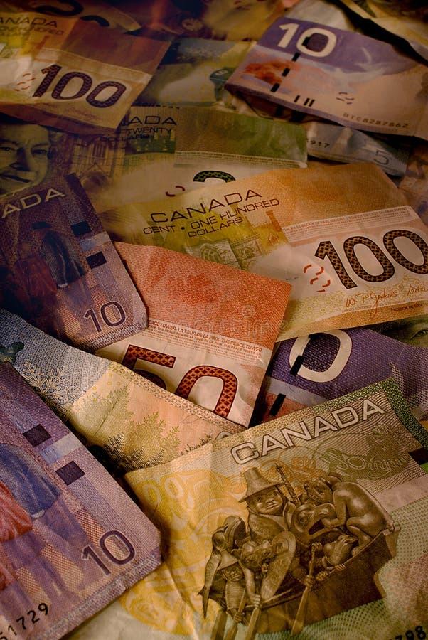 Contas usadas do dólar canadiano na luz morna foto de stock