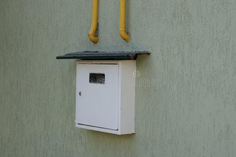 Contatore del gas con i tubi gialli su una parete grigia immagini stock