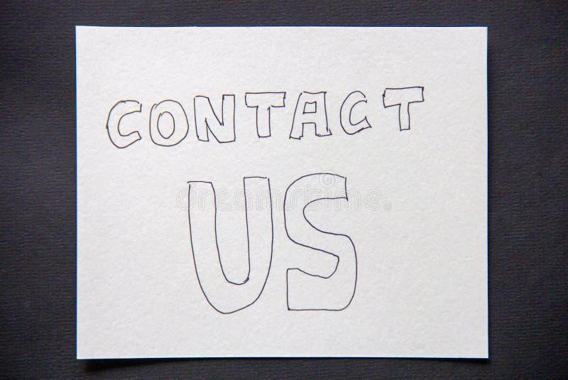 Contattici iscrizione scritta a mano sul Libro Bianco su buio fotografia stock libera da diritti