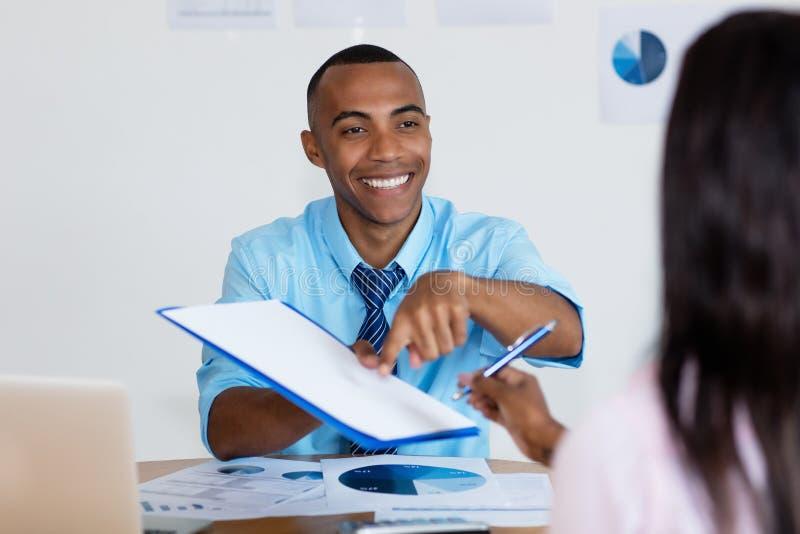 Contatto di firma della donna di affari afroamericana per il nuovo lavoro immagini stock
