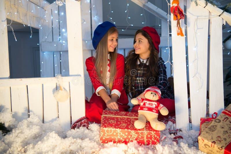 Conte de fées de Noël Petites filles mignonnes avec le cadeau de Noël Fond en bois de maison de jouet de boîte-cadeau de petites  photo libre de droits