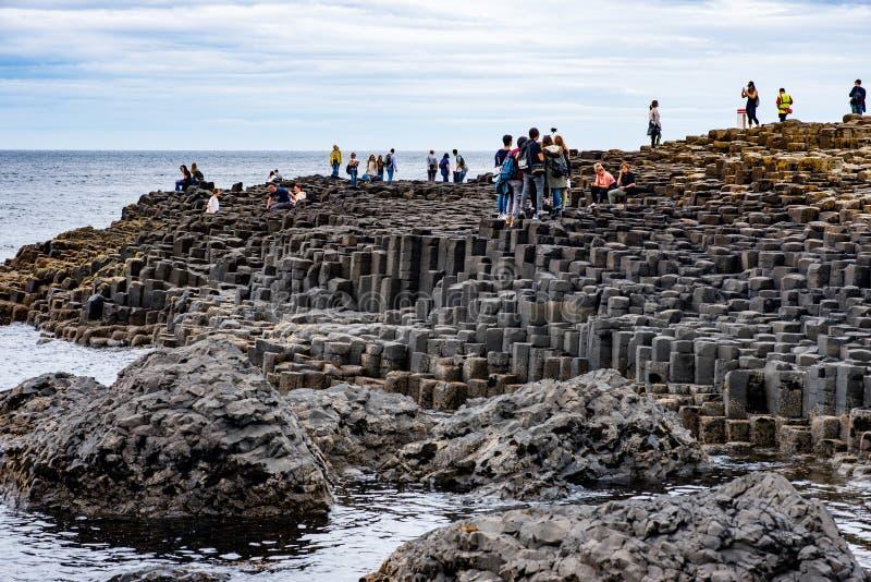 CONTEA ANTRIM, IRLANDA DEL NORD - 27 AGOSTO 2017: Gruppo di turisti che esplorano la strada soprelevata gigante del ` s fotografie stock