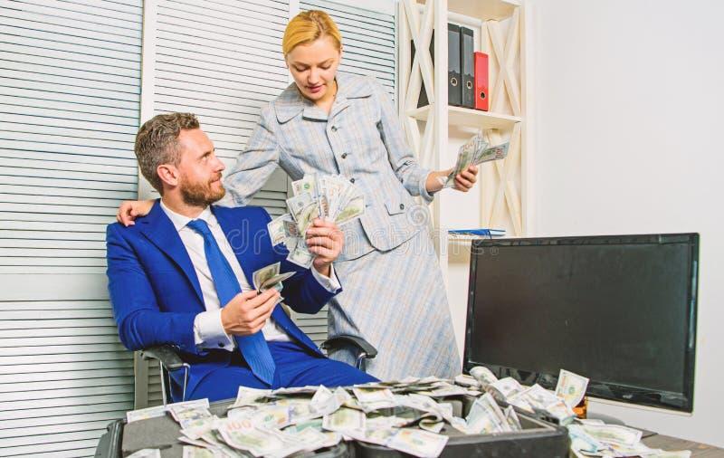 Conteggio del profitto dei soldi Uomo d'affari dell'uomo e segretario della donna con le banconote del dollaro del mucchio Concet immagini stock