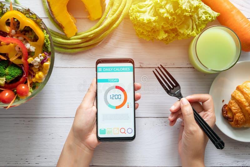 Conteggio di calorie, dieta, controllo di alimento e concetto di perdita di peso Donna che usando contro applicazione di caloria  immagini stock