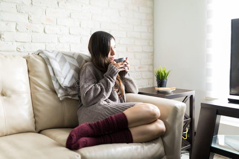 Contemplatieve Vrouw die verfrissen met Koffie stock foto