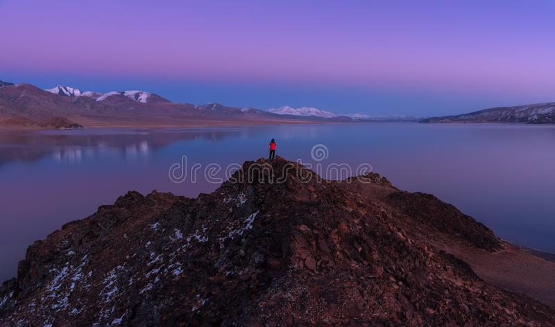 Contemplating Beauty: Mongolia, Alpine Lake Tolbo-Nuur 2079 M., Art Photography.Man In Red Jacket Standing On Red Rock And Photo. Graphs A Beautiful Lilac Late royalty free stock images