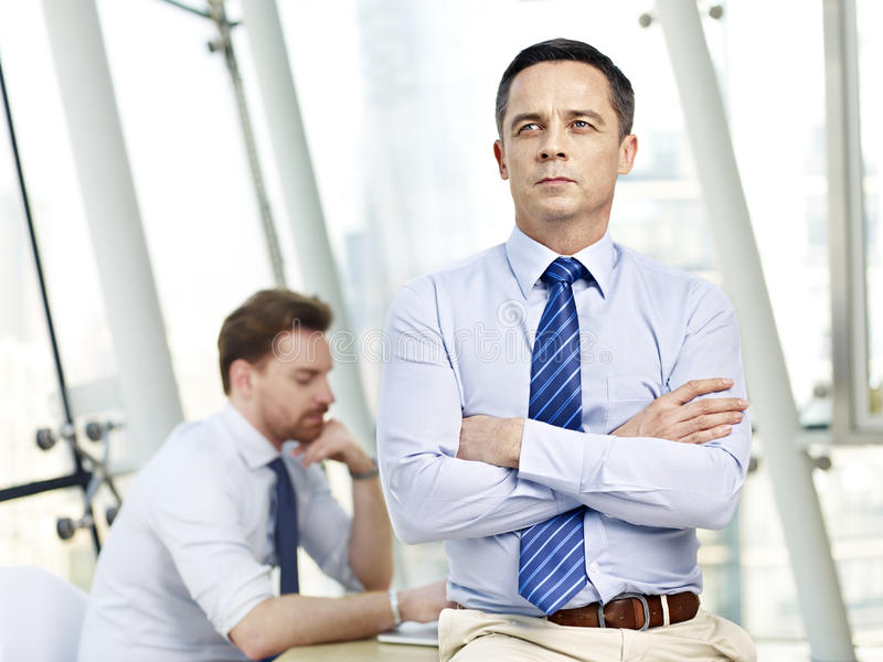 Contemplating business person sitting on desk in office royalty free stock images