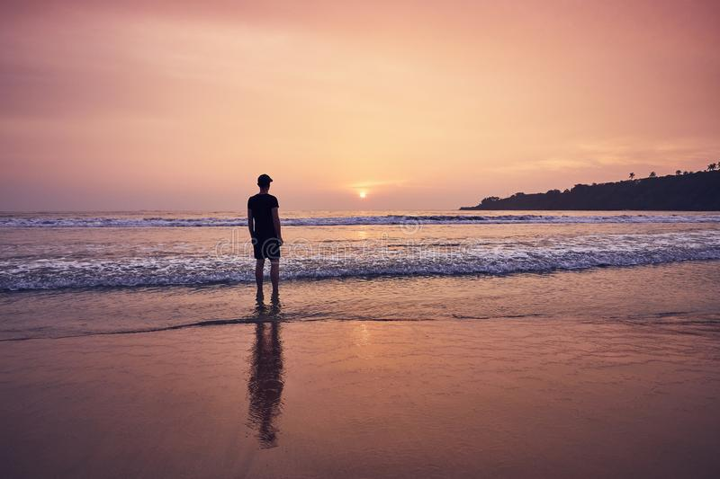 Contemplation during beautiful sunrise. Young man on idyllic sand beach near Tangalle in Sri Lanka royalty free stock photo