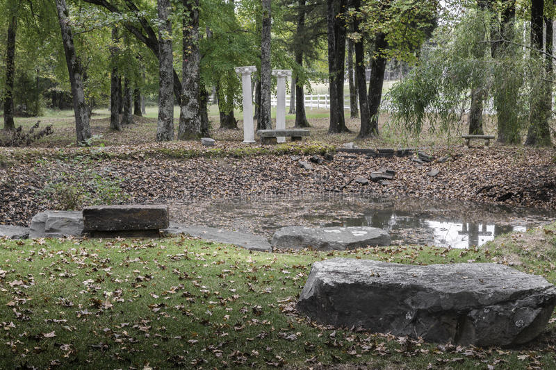 Contemplation pond in Ozark Mountains of Arkansas. Serene pond for contemplation and relaxation with rocks, pillars, and benches for viewing reflection in the stock photography