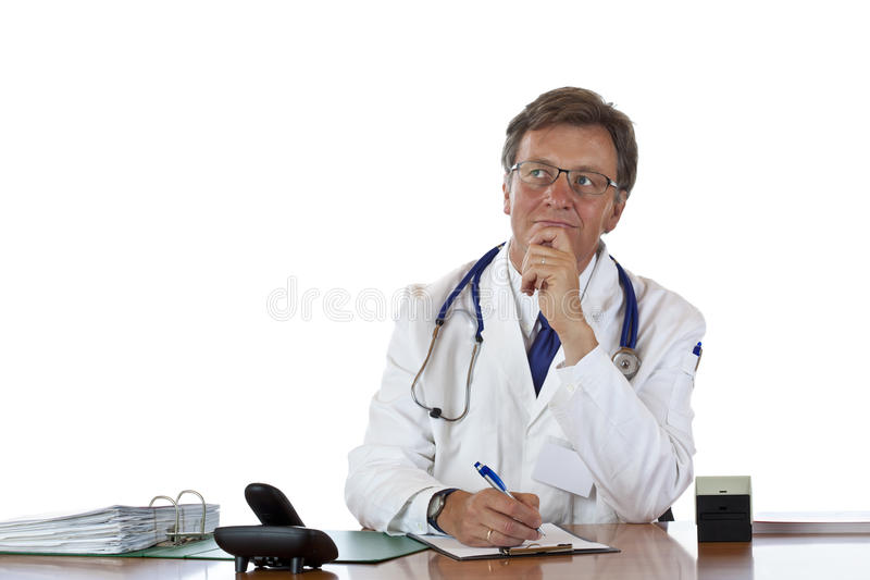 Contemplative aged doctor at desk. Writes prescription.Isolated on white background stock photography