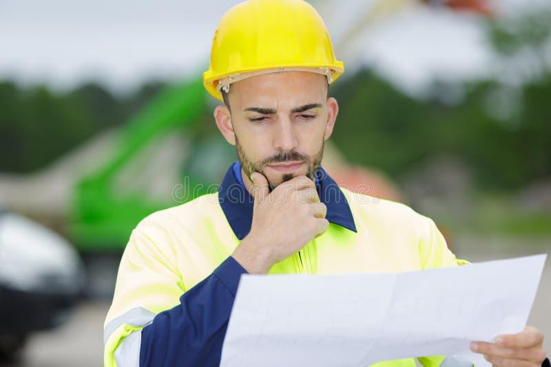 Contemplative Builder som tittar på pappersarbete arkivfoton