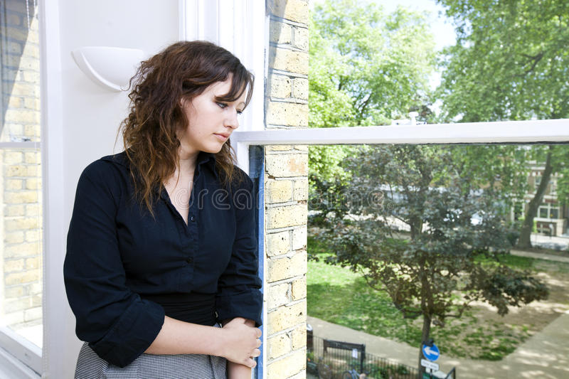 Contemplative businesswoman looking out the window stock image