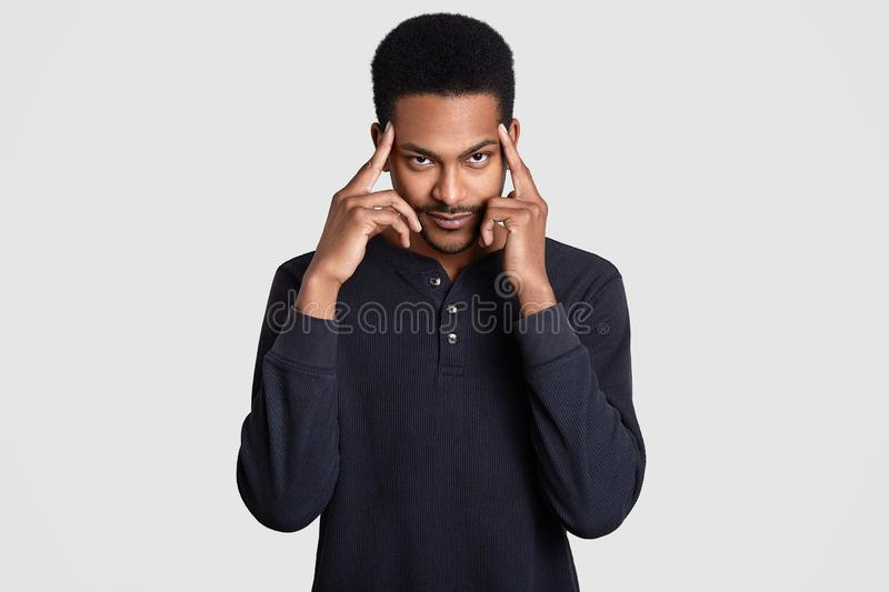 Contemplative dark skinned man keeps both index fingers on temples, thinks about something, tries to concentrate and remember some. Information, dressed in stock photos