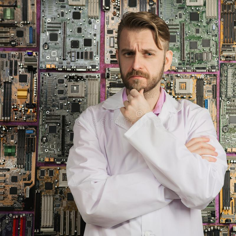 Contemplative electronics engineer stands near the wall of motherboards. Contemplative bearded electronics engineer stands near the wall of motherboards stock images