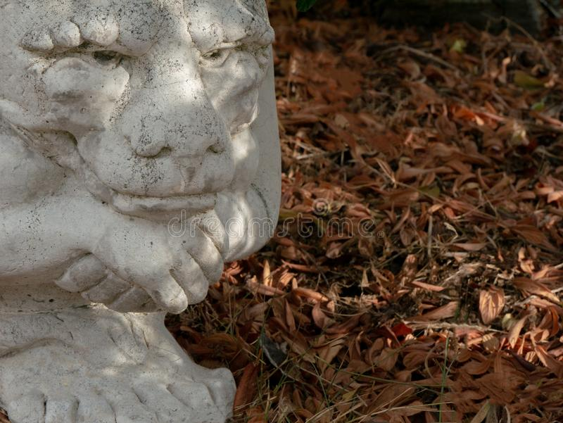 Contemplative garden gargoyle with brown fall leaves. Brooding, contemplative, or peaceful garden gargoyle statuette with a background of fallen brown leaves stock image