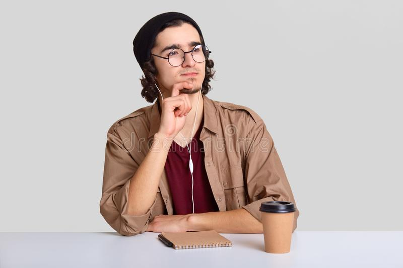 Contemplative hispter keeps hand on chin, looks with dreamy expression aside, has small beard, wears casual clothes, listens audio. With unrecognizable device stock photography