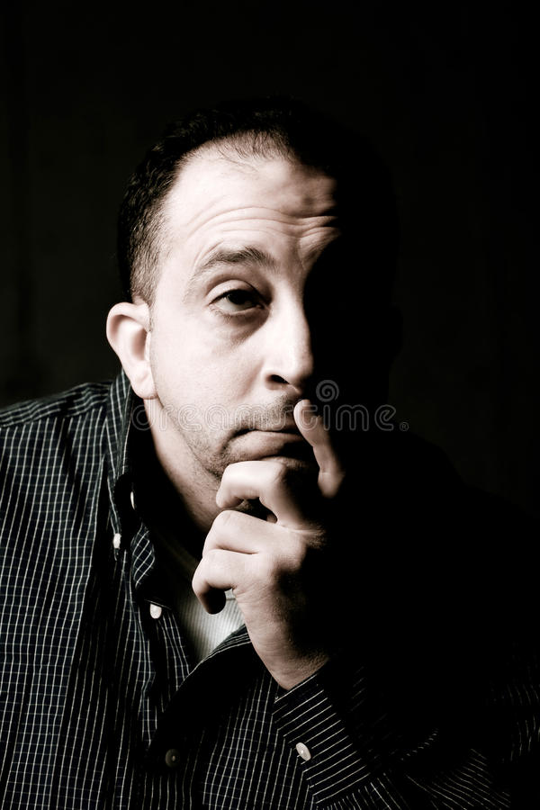 Contemplative Man. High contrast portrait of a middle aged man with a contemplative look on his face. He could be worried or anxious about something on his mind royalty free stock image
