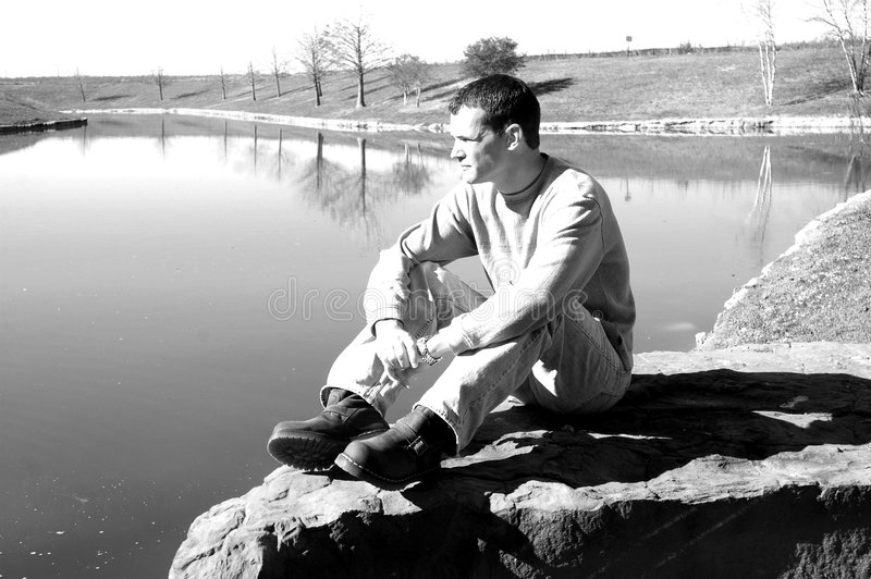 Contemplative Man. A man in casual clothing sits alone on a rock by a pond. Man sitting in a park or nature park. Man being thoughtful: occupied with or given to stock image