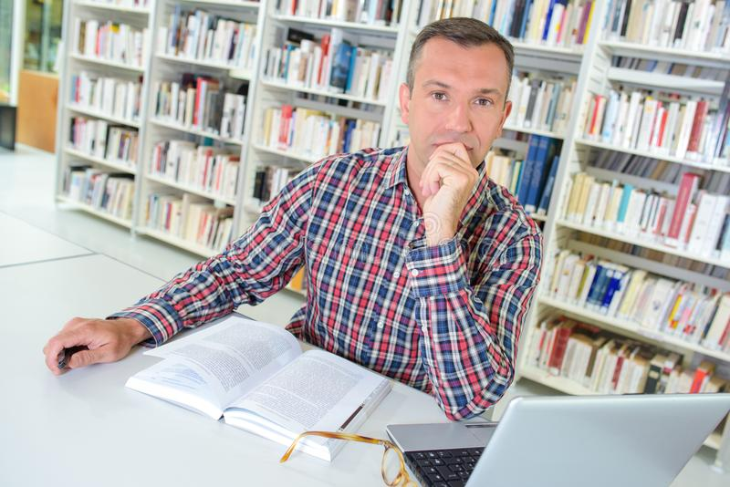 Contemplative man in library. Man stock photos