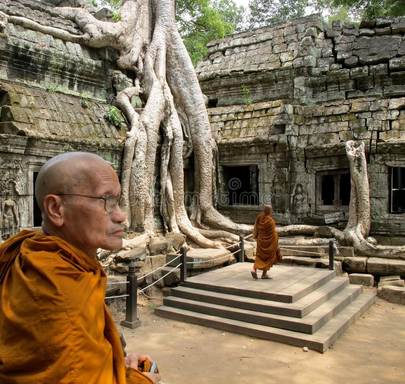 Contemplative monk at Angkor Wat. Contemplative Monk in an orange cowl at the temples of Angkor Wat in Cambodia stock image