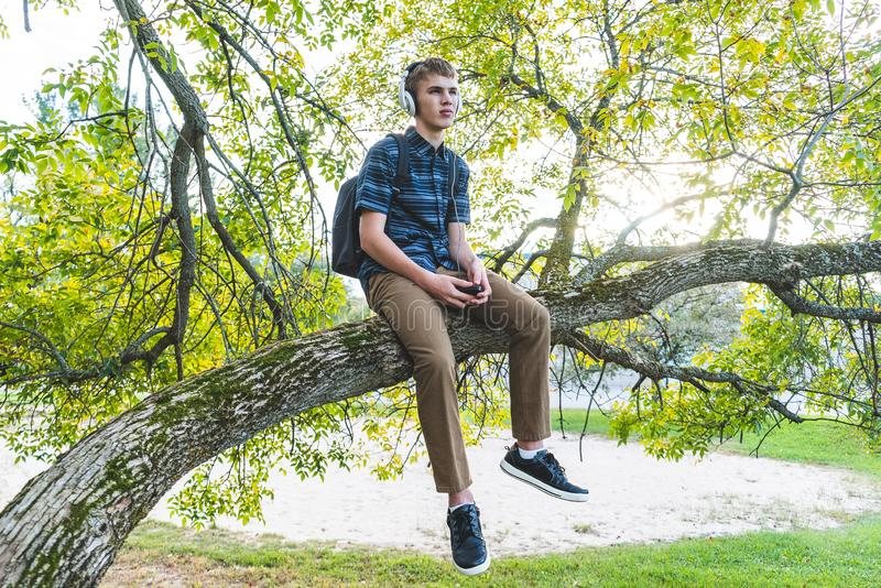 Contemplative student listening to music. The image displays a contemplative student sitting on a tree branch while listening to music through his headphones royalty free stock photography