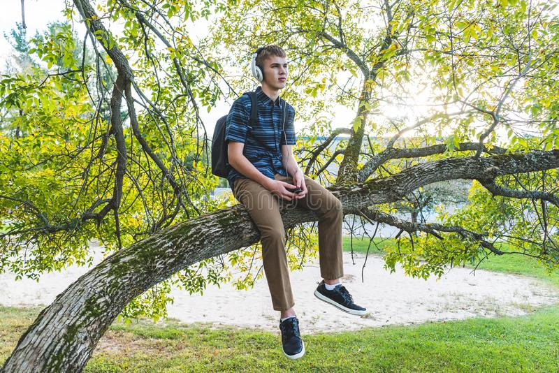 Contemplative student listening to music. The image displays a contemplative student sitting on a tree branch while listening to music through his headphones royalty free stock image