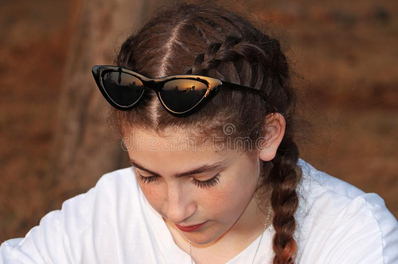 A contemplative teenage girl. With sunglasses in the forest at sunset stock images