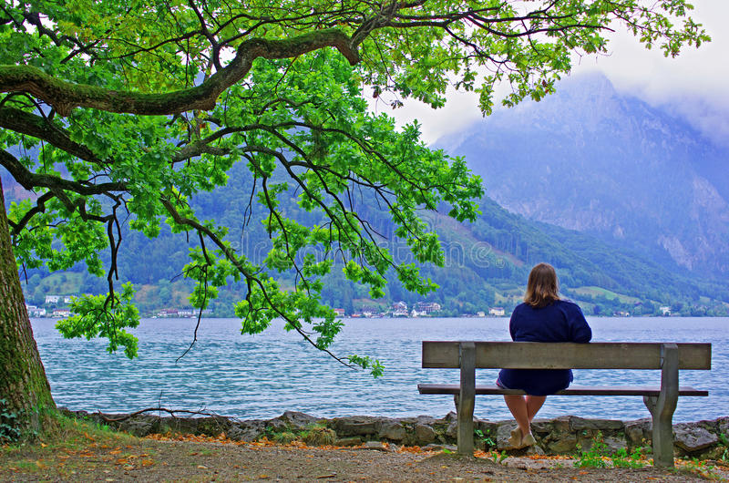 Contemplative Woman. Alone on bench admiring the landscape stock photos