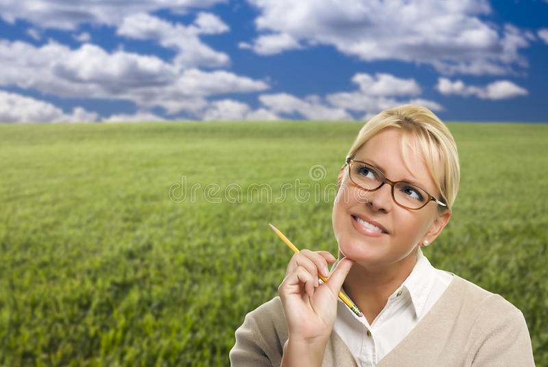 Contemplative Woman in Grass Field Looking Up and Over. To the Side stock image