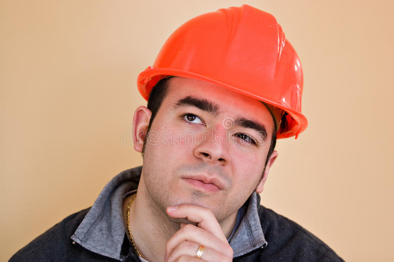 Contemplative Worker. A young construction working with a pensive or contemplative look thinking hard about something stock photo