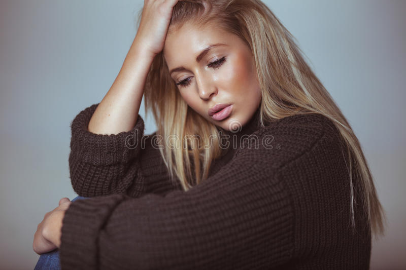 Contemplative young woman in sweater. Pretty young woman looking down in thought royalty free stock image