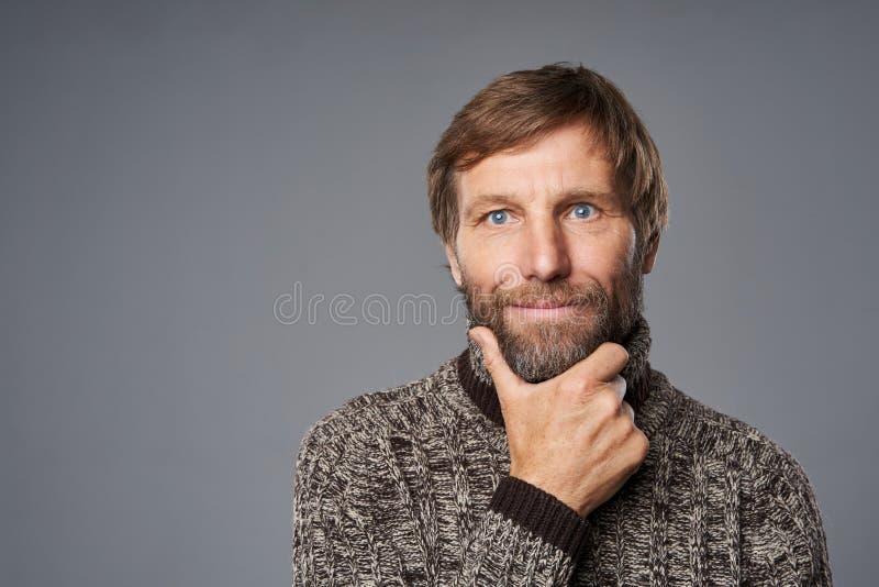 Contempler un homme mature en pull chaud avec la main sur le menton images libres de droits