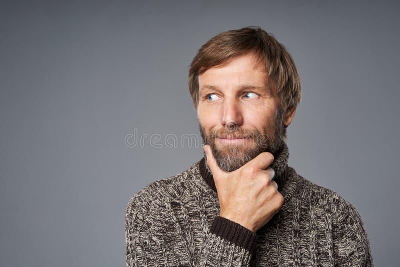 Contempler un homme mature en pull chaud avec la main sur le menton photo stock