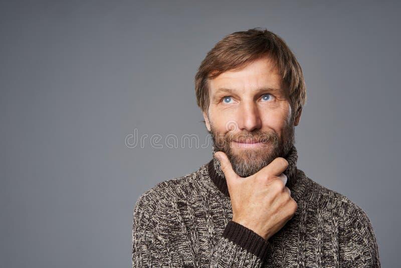Contempler un homme mature en pull chaud avec la main sur le menton photos libres de droits