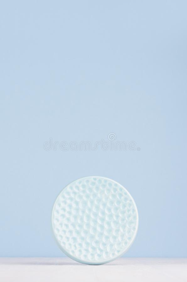 Contemporary art abstract background, interior - decorative ceramic smooth ribbed sphere in soft pastel blue color on white wood. Contemporary art abstract stock photography