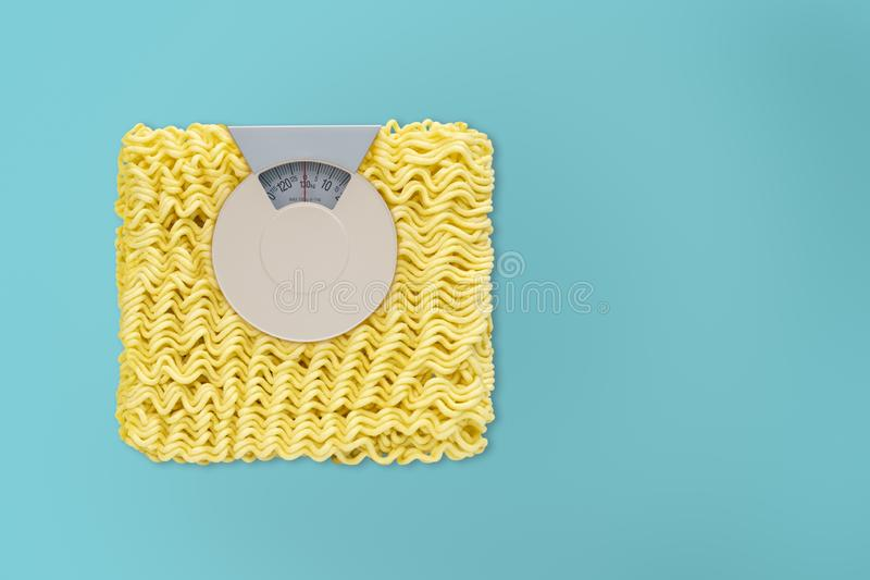 Contemporary art-Weight scale in the form of noodles on blue background with copy space royalty free stock photos