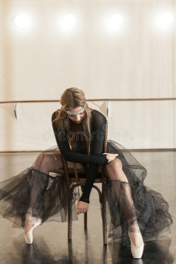 Contemporary ballet dancer on a wooden chair on a repetition. Beautiful female contemporary ballet dancer in black wear posing on a wooden chair on a repetition stock image
