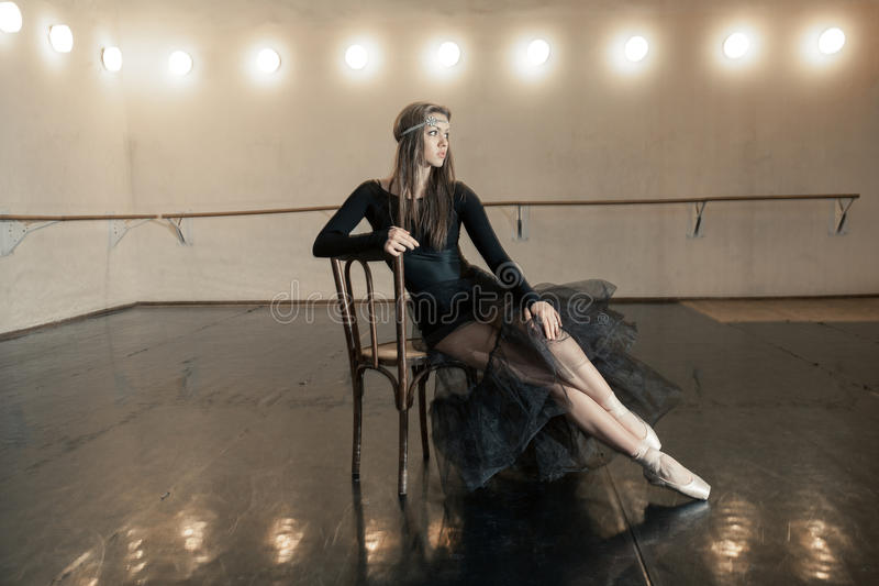 Contemporary ballet dancer on a wooden chair on a repetition. Beautiful female contemporary ballet dancer in black wear posing on a wooden chair on a repetition royalty free stock image