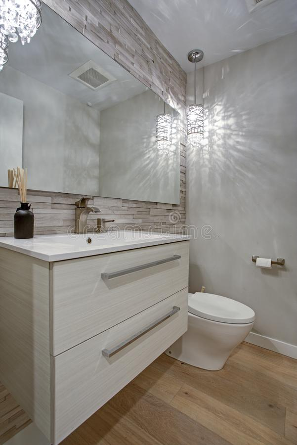 Contemporary bathroom design with taupe linear tiles accent wall. Contemporary bathroom design with taupe linear stacked tiles backsplash illuminated by royalty free stock image