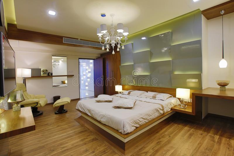Contemporary bedroom interior. Bedroom interior with leather chair and modern lighting designed by Amar Architecture and Designs Pvt Ltd in Calicut, India royalty free stock photo