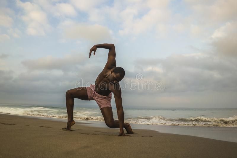 Contemporary dance choreographer and dancer doing ballet beach workout . a young attractive and athletic black African American. Man dancing on sunrise doing royalty free stock photos