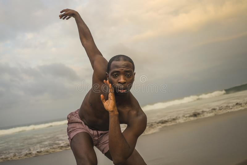 Contemporary dance choreographer and dancer doing ballet beach workout . a young attractive and athletic black African American. Man dancing on sunrise doing royalty free stock images
