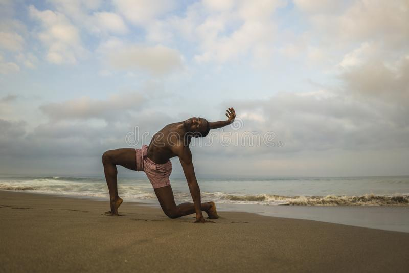 Contemporary dance choreographer and dancer doing ballet beach workout . a young attractive and athletic black African American. Man dancing on sunrise doing stock photography