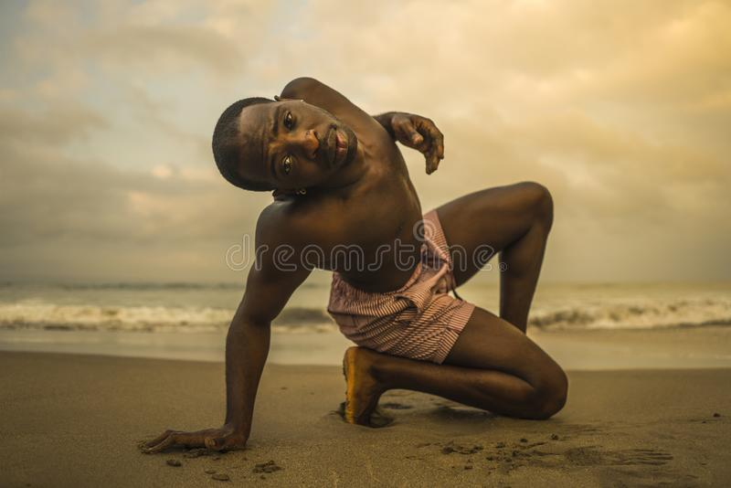Contemporary dance choreographer and dancer doing ballet beach workout . a young attractive and athletic black African American. Man dancing on sunrise doing royalty free stock photo