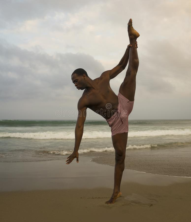 Contemporary dance choreographer and dancer doing ballet beach workout . a young attractive and athletic black African American. Man dancing on sunrise doing stock photos
