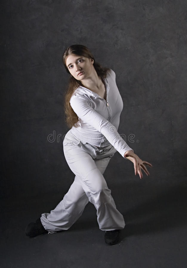 Contemporary dancer. Young woman posing against gray concrete wall royalty free stock image