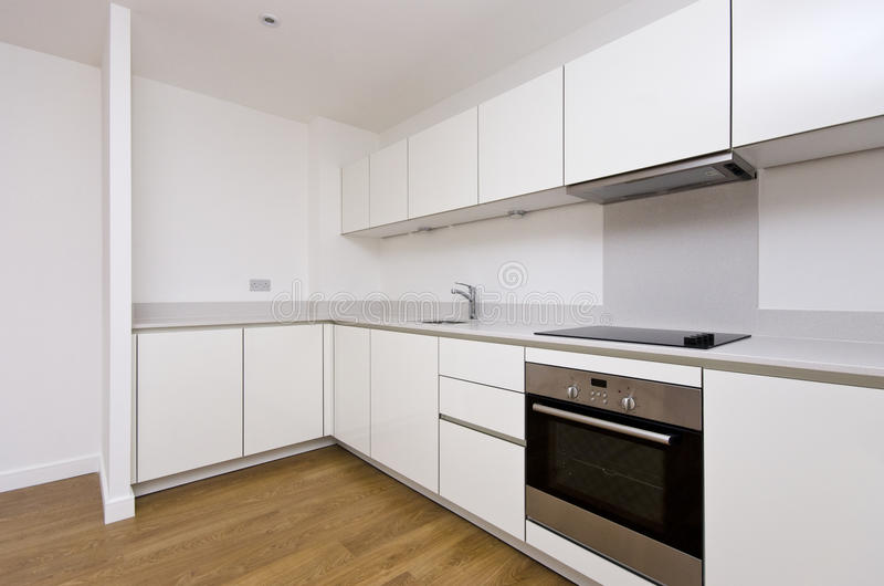 Contemporary fully fitted kitchen in white royalty free stock photos