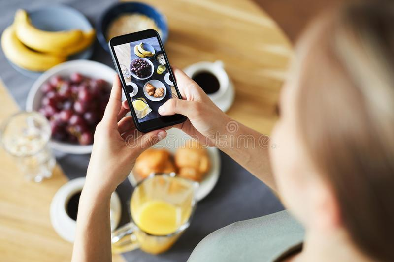 Contemporary girl with smartphone taking shot of her served table royalty free stock photos
